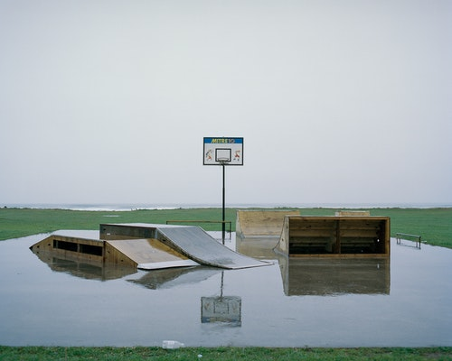 The sky becomes the sea, behind a recreation area at Carter's Beach, west of Westport. With one concrete slab surrounded by rain-swamped grassed land, skate ramps share a space with a basketball hoop.